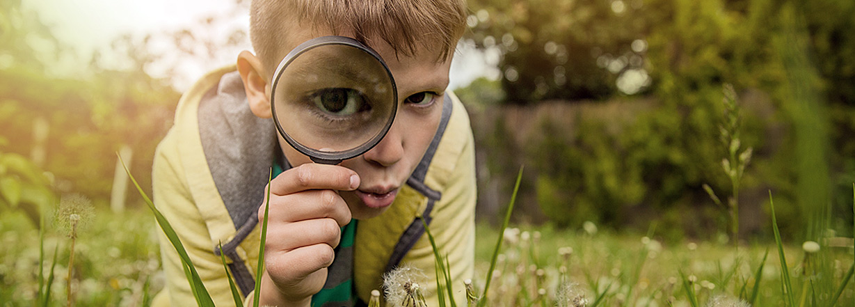 A little boy holding a magnifying glass.